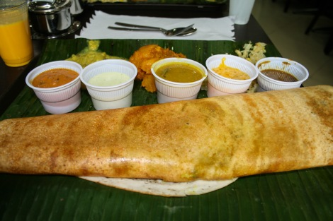 Vegetable filled dosa pancake on a green banana leaf.