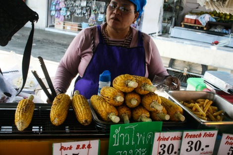 Woman selling ears of corn in a market in Koh Phangan, Thailand.