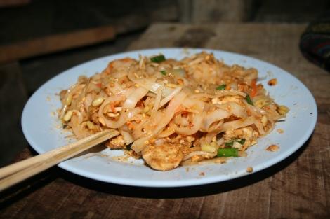 Noodles, pad thai on a blue plate.